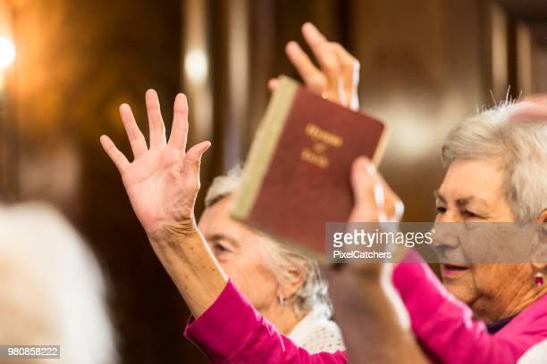 close-up de mãos sênior feminino erguidas em louvor na igreja - congregação - fotografias e filmes do acervo