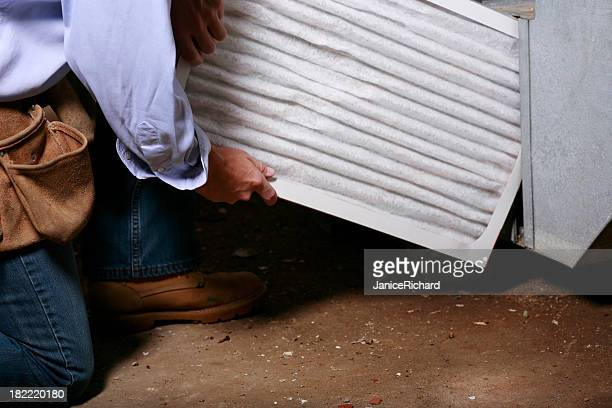 Close up of service man changing furnace air filter