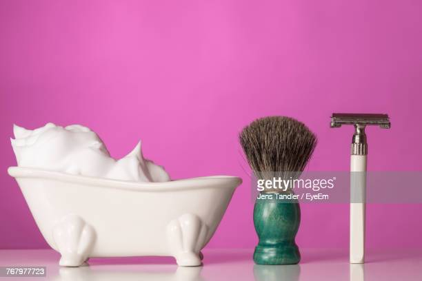 close up of shaving cream in bathtub by brush and razor - razor stock photos and pictures