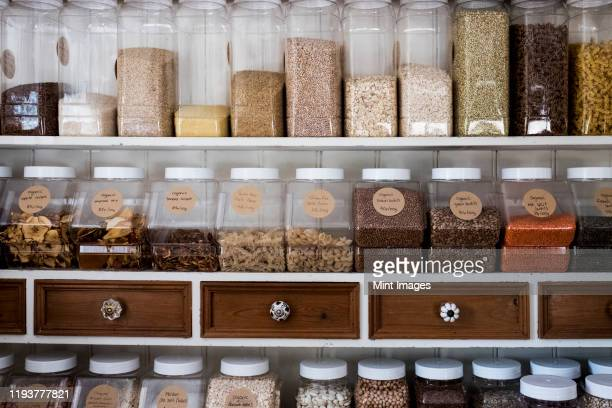 close up of shelves with a selection of pasta, legumes and grains in glass jars. - jar stock pictures, royalty-free photos & images