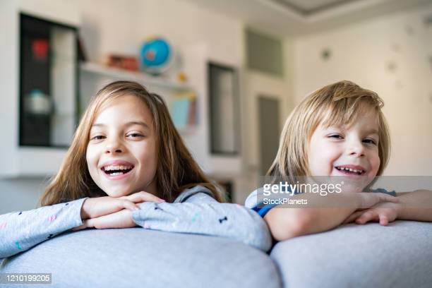 close up of sibling in living room - sister stock pictures, royalty-free photos & images