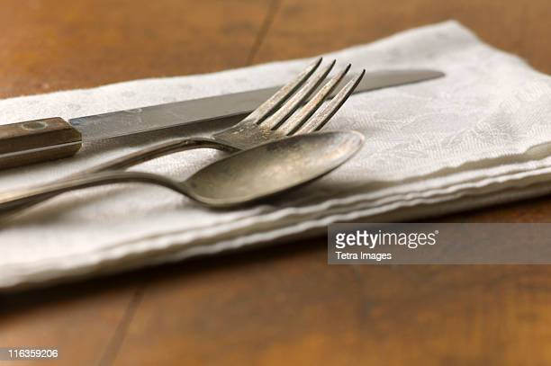 Close up of silver forks, knife and spoon on napkin