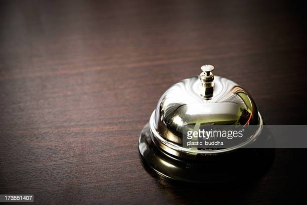 Close up of silver service bell on dark wooden desk
