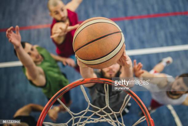 close up of slam dunk during basketball match. - basketball team stock pictures, royalty-free photos & images