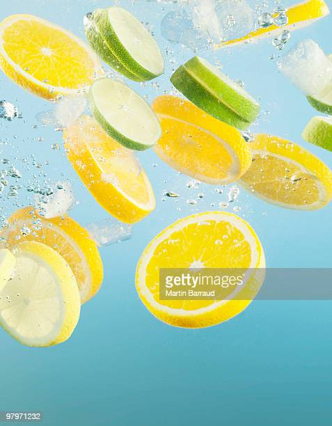close up of sliced lemons and limes splashing in water - lemon fruit stock pictures, royalty-free photos & images