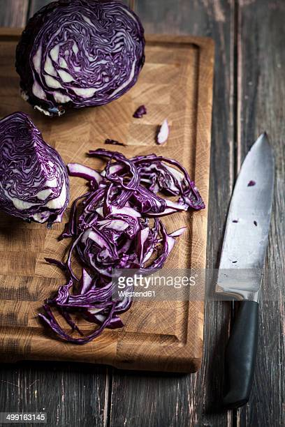 close up of sliced red cabbage on chopping board and knife - rodekool stockfoto's en -beelden