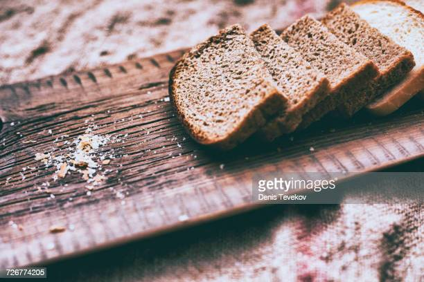 Close up of slices of bread and crumbs on wooden tray