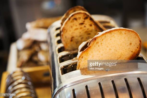 close up of slices of bread in a stainless steel toaster. - bread stock pictures, royalty-free photos & images