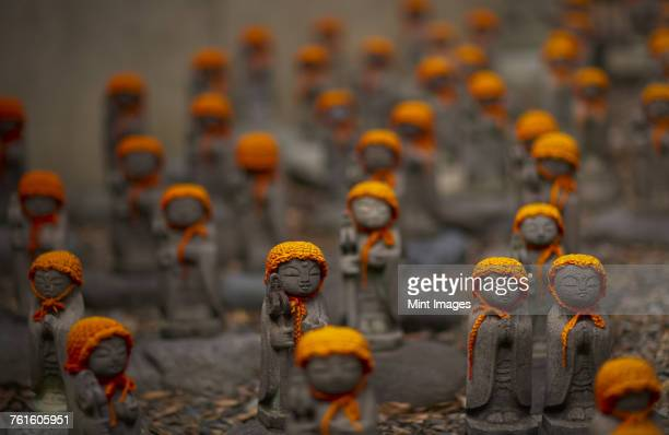 Close up of small brown Buddhist Jizo, Japanese stone statues, wearing orange hats, at Daienji, Tokyo, Japan.