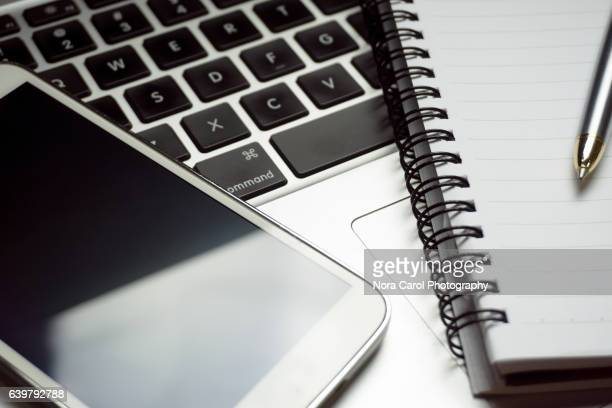close up of smartphone, pen and notepad on a computer keyboard - elektronische organiser stockfoto's en -beelden