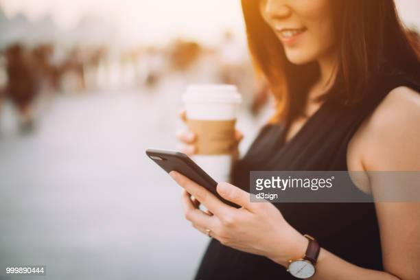 close up of smiling beautiful pregnant woman enjoying coffee and using mobile phone in city at sunset - pregnant coffee stock pictures, royalty-free photos & images