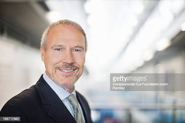 Close up of smiling businessman in office hallway