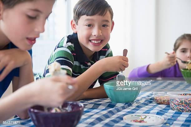 Close up of smiling children eating ice cream sundaes