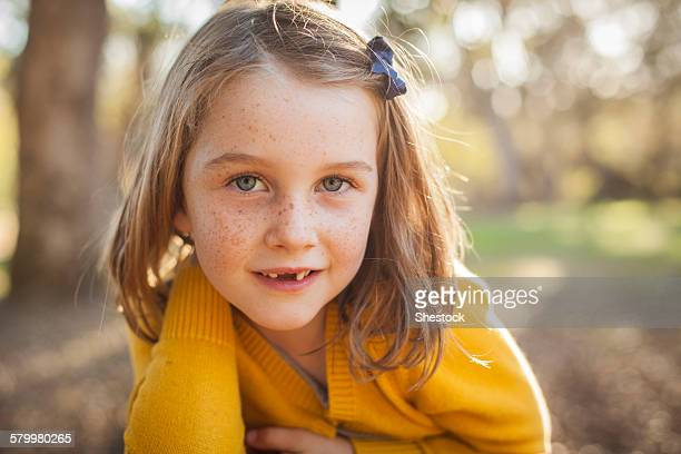 Close up of smiling girl laying in field