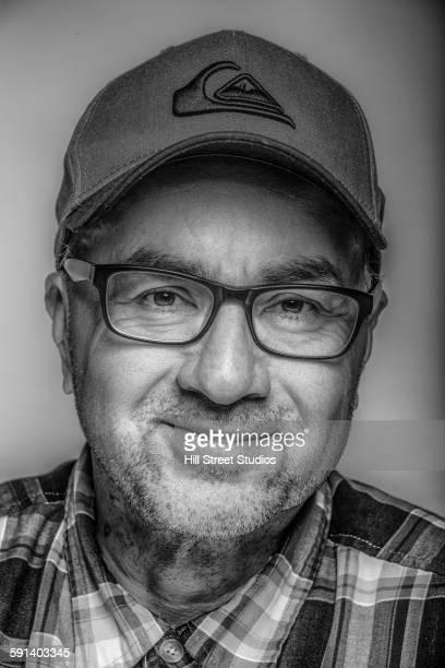 Close up of smiling Hispanic man wearing eyeglasses and cap
