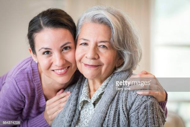 Close up of smiling mother and daughter hugging