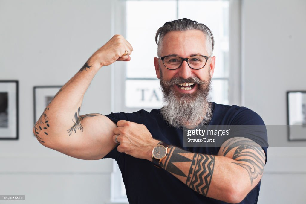 Close up of smiling muscular Caucasian hipster man flexing biceps : Stock Photo