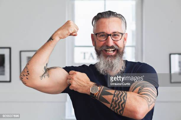 Close up of smiling muscular Caucasian hipster man flexing biceps