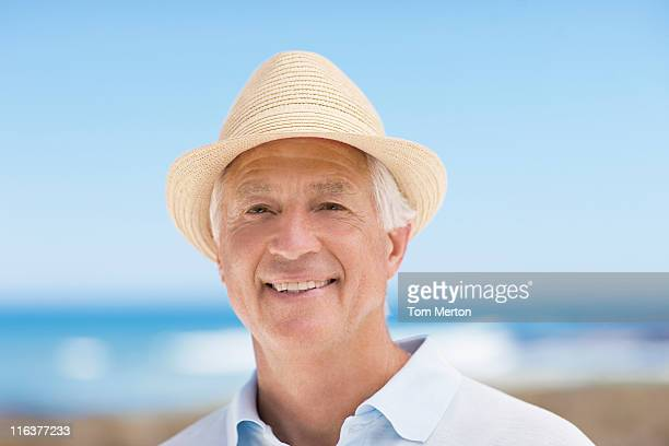 Gros plan d'un homme senior souriant de chapeau