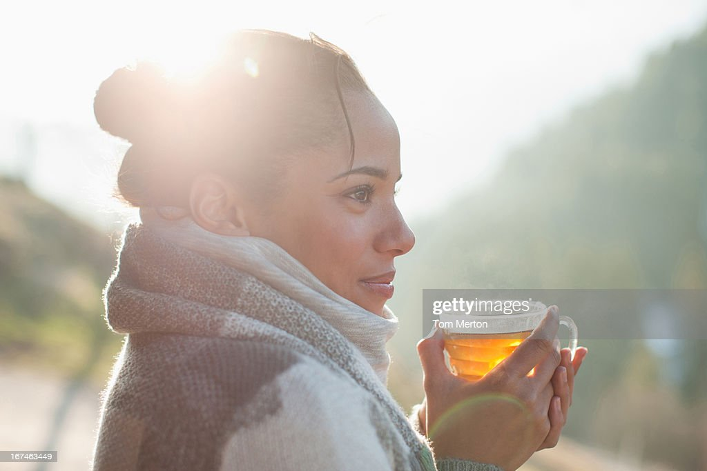 Close up of smiling woman drinking tea outdoors : Stock Photo