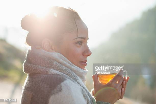 close up of smiling woman drinking tea outdoors - hot tea stock pictures, royalty-free photos & images
