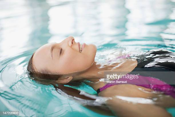 Close up of smiling woman floating on back in swimming pool