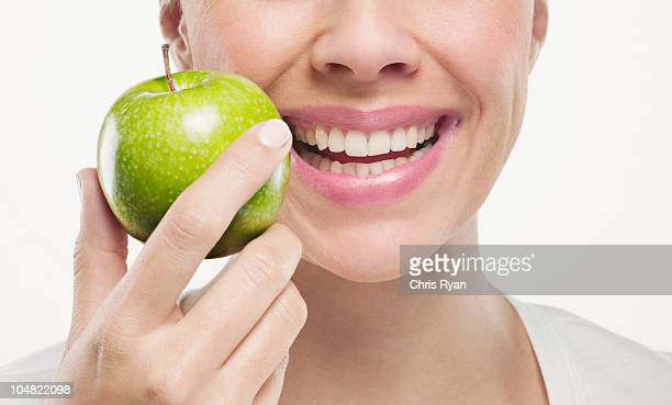 Close up of smiling woman holding green apple