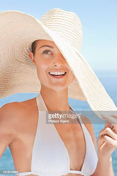 close up of smiling woman in large sun hat on beach - sun hat stock pictures, royalty-free photos & images