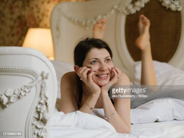 close up of smiling woman lying on bed - showus stock-fotos und bilder