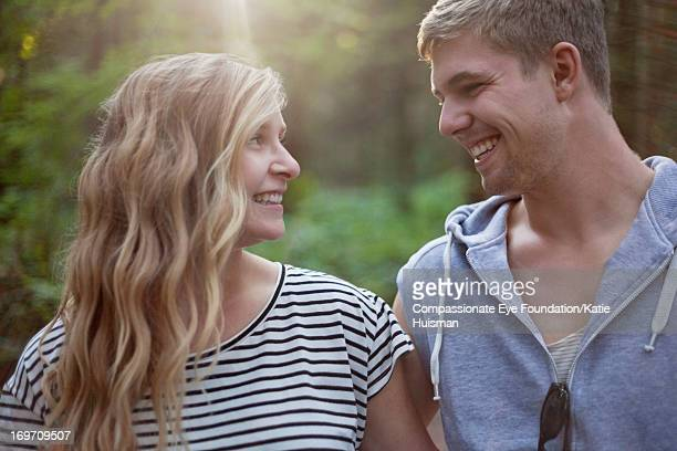 Close up of smiling young couple in woods