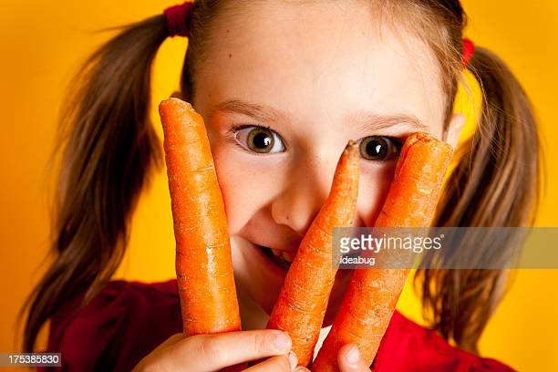 Close Up of Smiling Young Girl Holding Three Carrots