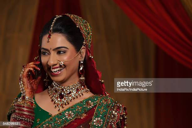Close up of smiling young Indian woman talking on cell phone while looking away