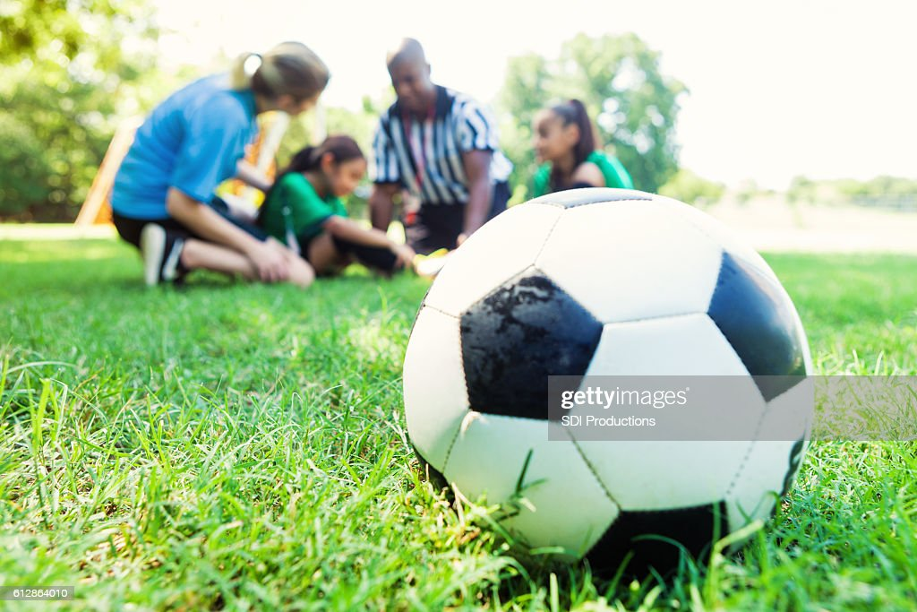 Close up of soccer ball wilth injured player in background : Stock Photo