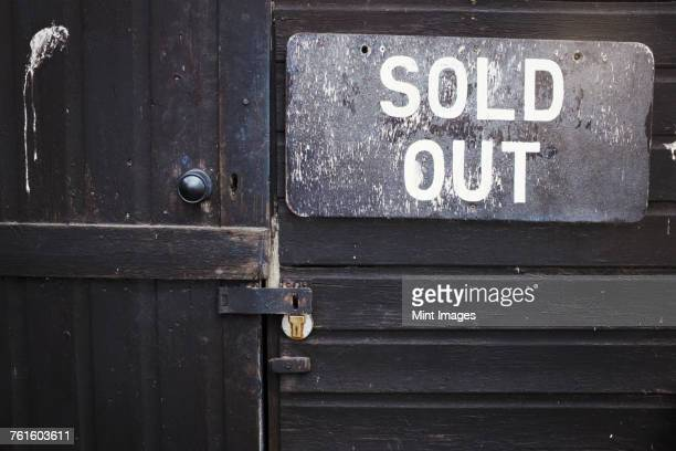 close up of sold out sign on black wooden wall beside a closed door. - sold out stock pictures, royalty-free photos & images