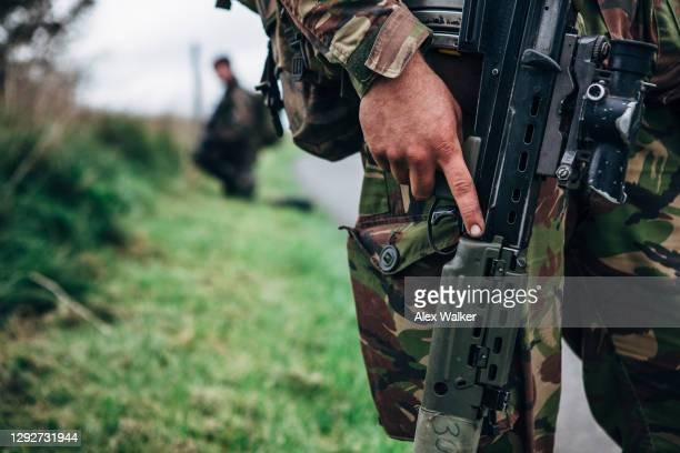 close up of soldier holding assault rifle - gun stock pictures, royalty-free photos & images