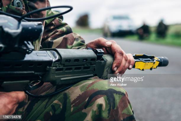 close up of soldier holding assault rifle with blank firing adaptor - royal marines stock pictures, royalty-free photos & images