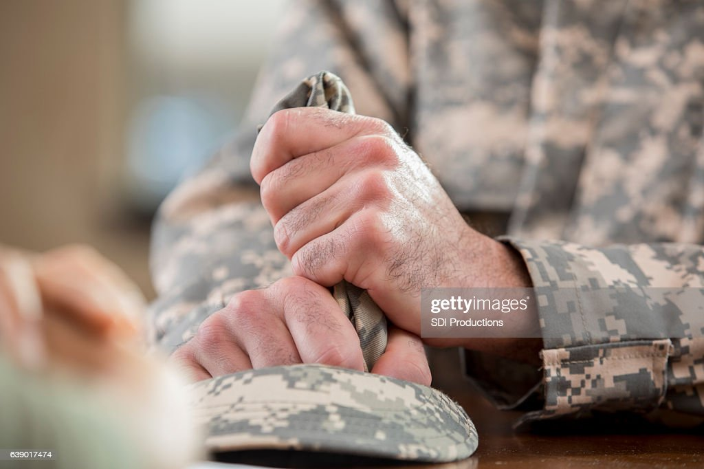 Close up of soldier's hands holding hat in counseling session : Stock Photo