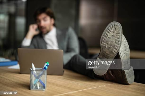 オフィスでリラックスしたビジネスマンの靴の裏をクローズアップ。 - 靴底 ストックフォトと画像