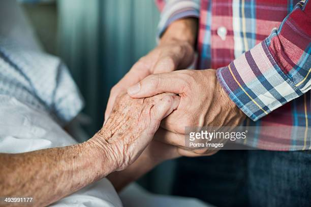 close up of son holding his mothers hands - cuidado fotografías e imágenes de stock