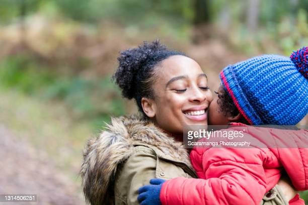 close up of son kissing mother in forest - warm clothing stock pictures, royalty-free photos & images