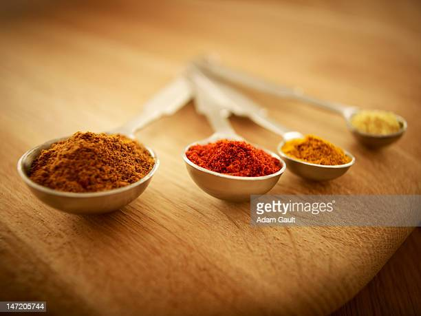 close up of spices in measuring spoons - measuring spoon stock pictures, royalty-free photos & images