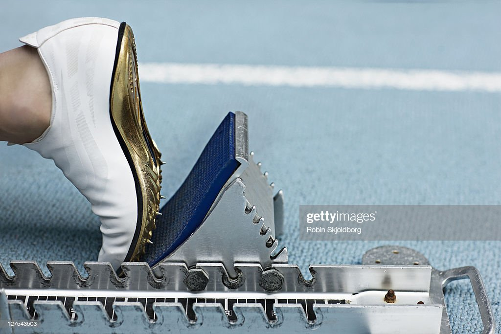 Close up of spiked shoe at start block : Stock Photo