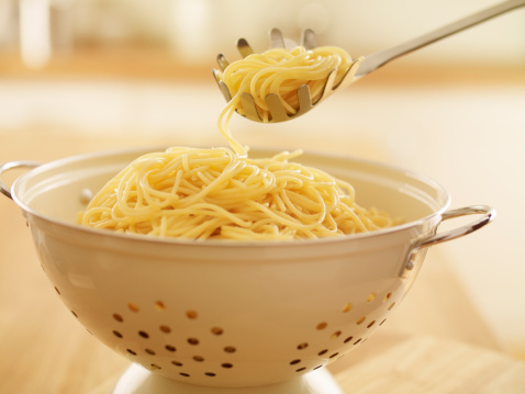Close up of spoon scooping spaghetti in colander - gettyimageskorea