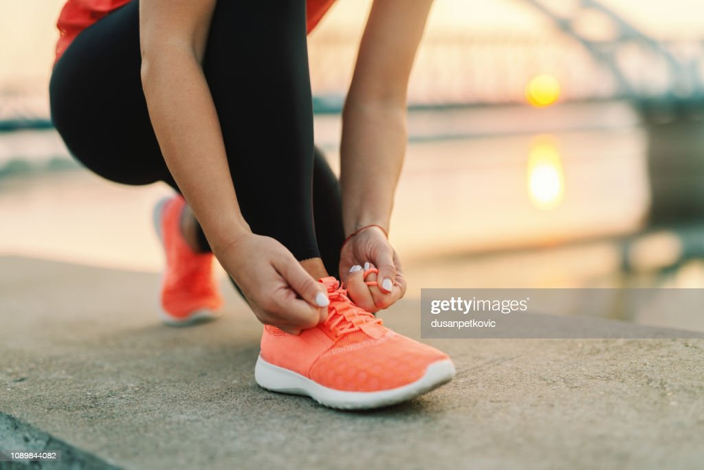 Close up of sporty woman tying shoelace while kneeling outdoor, In background bridge. Fitness outdoors concept. : Stock Photo