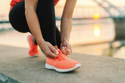Close up of sporty woman tying shoelace while kneeling outdoor, In background bridge. Fitness outdoors concept. 1089844082