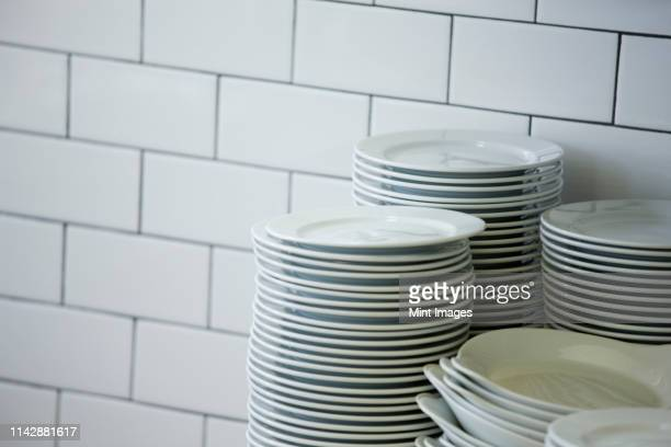 close up of stacked plates in restaurant kitchen - 積み重ねる ストックフォトと画像