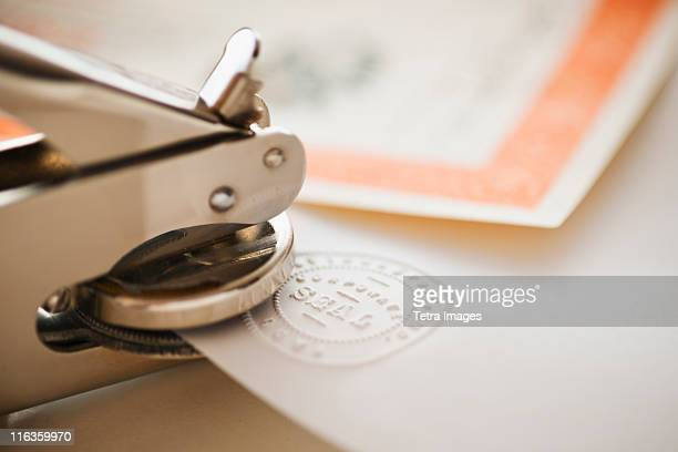 close up of stamper making seal on paper - seal stock pictures, royalty-free photos & images
