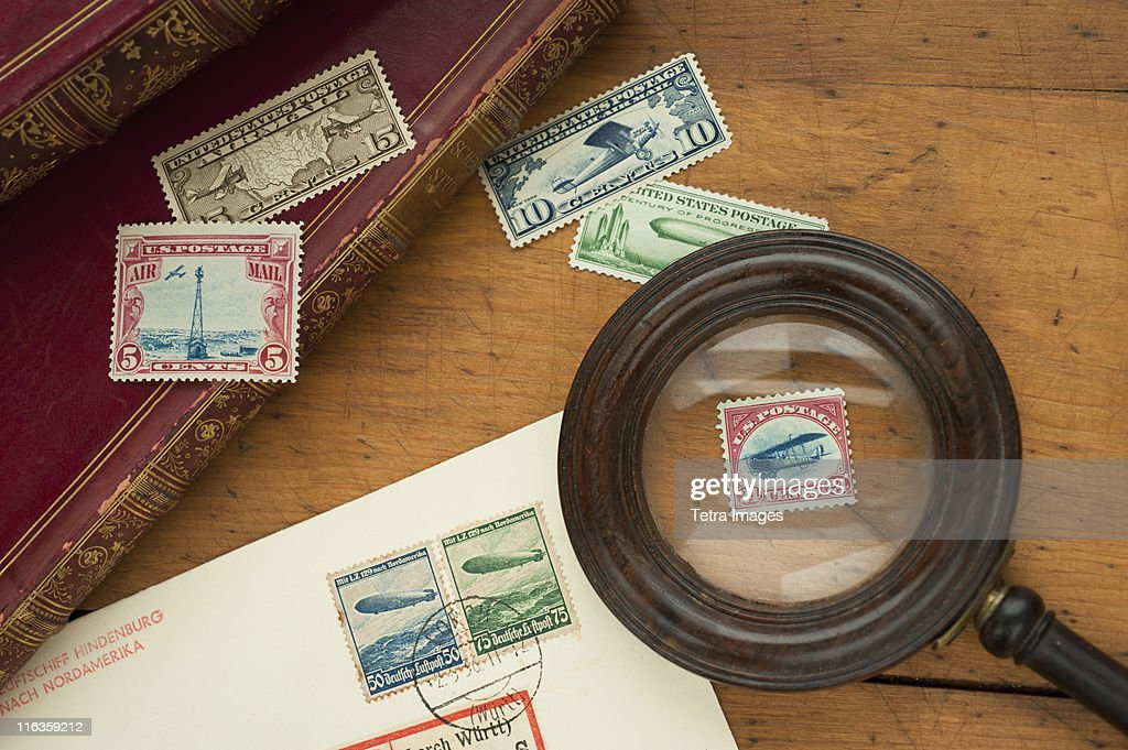Close up of stamps collection and magnifying glass : Stock Photo