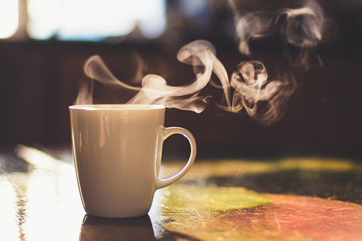 Close up of steaming cup of coffee or tea on vintage table - early morning breakfast on rustic background 1137365972