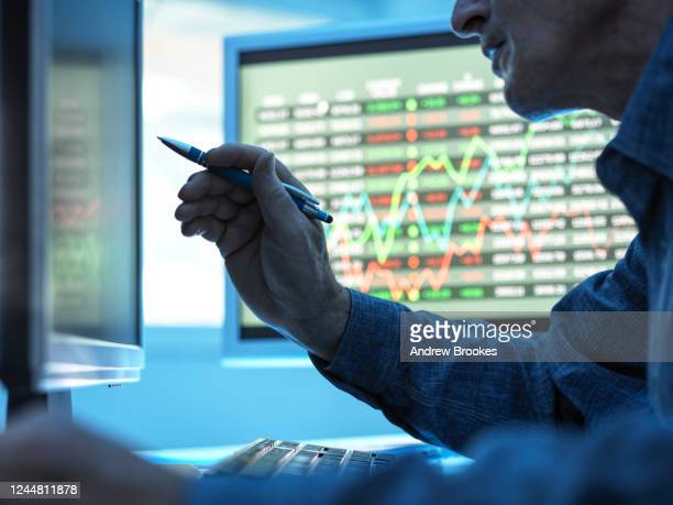 close up of stock market trader analysing share price data on the screen. - stock market stock pictures, royalty-free photos & images